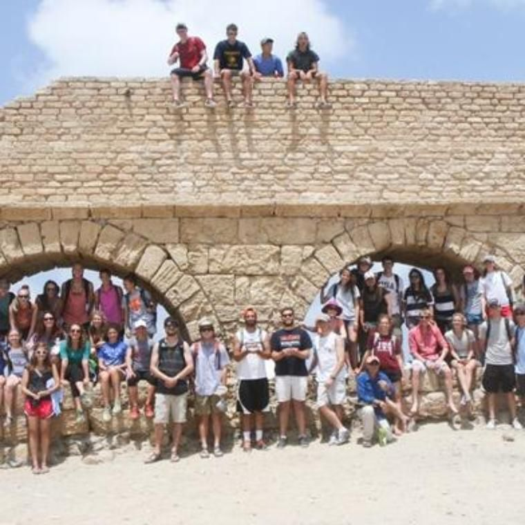 Students by a holy land structure