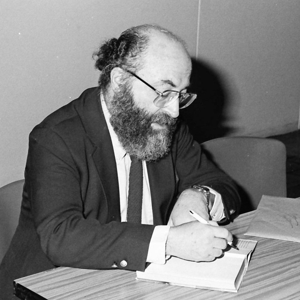 Black-and-white photo of Chaim Potok writing in a book, 1985