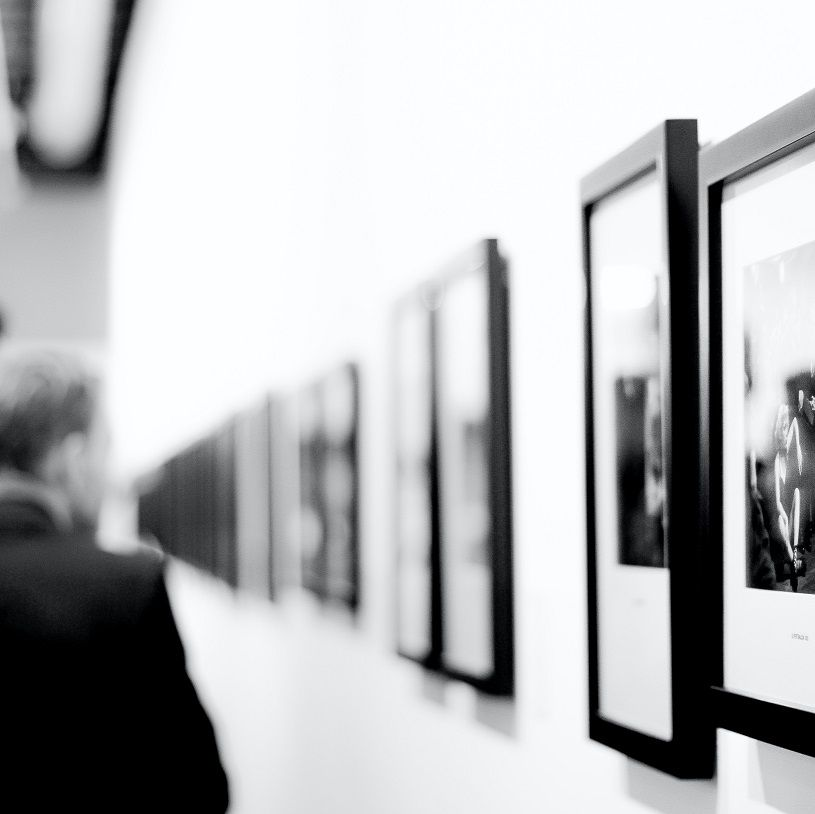Framed art pieces in a gallery with people
