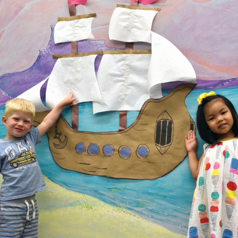 ec students pointing to paper boat