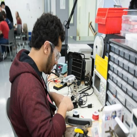 Engineering student works on project with lab glasses