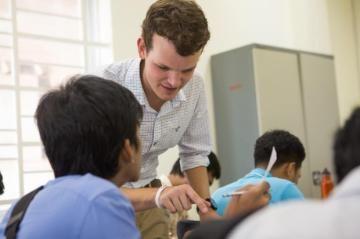 A young man teaching students