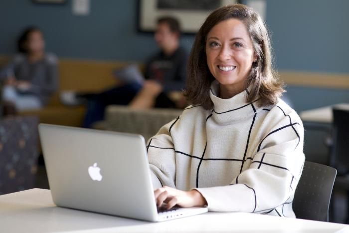 A woman sitting at a laptop and smiling at a camera