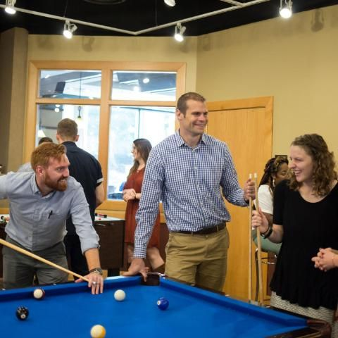 Justin Heth playing pool with MA in HESD Students