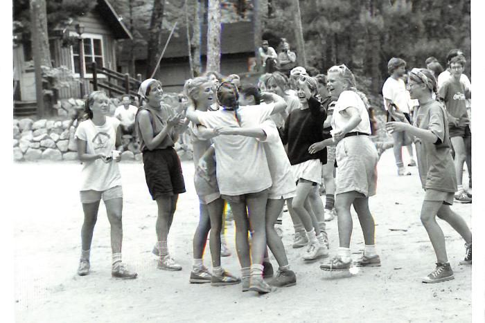 High road women celebrate under a welcome home banner at HoneyRock