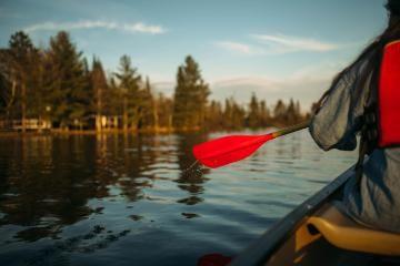 Vanguard paddling down long lake at HoneyRock in Three Lakes, WI