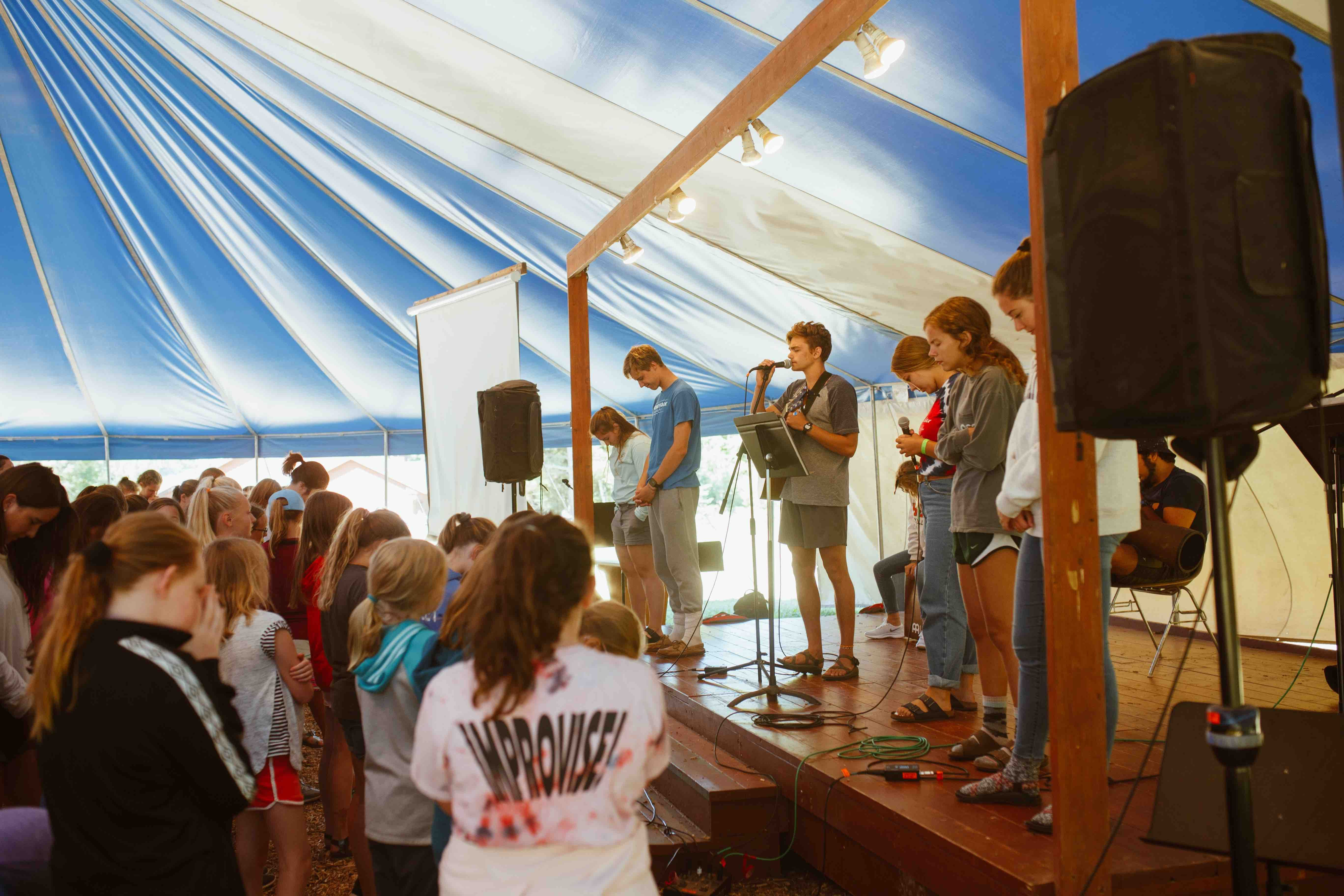 Our third to eighth graders worship in the blue and white tent and are led by cabin leaders.