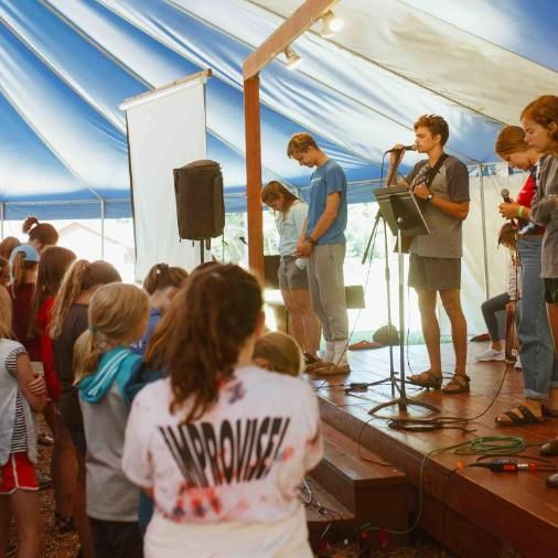After group games, Day Campers sing fun worship songs in the blue and white tent.