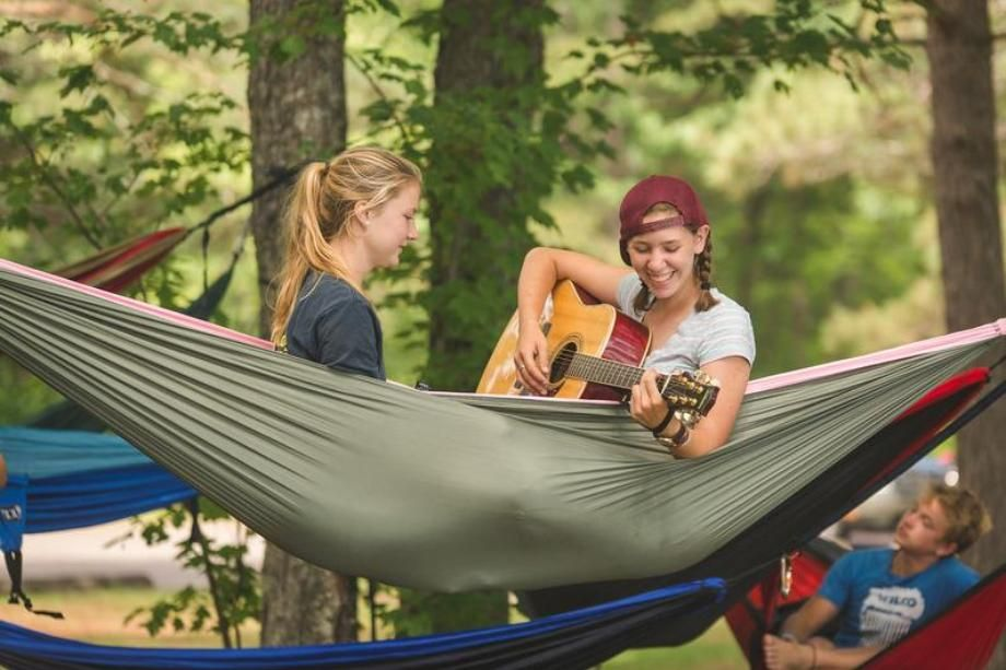 campers in hammock playing guitar