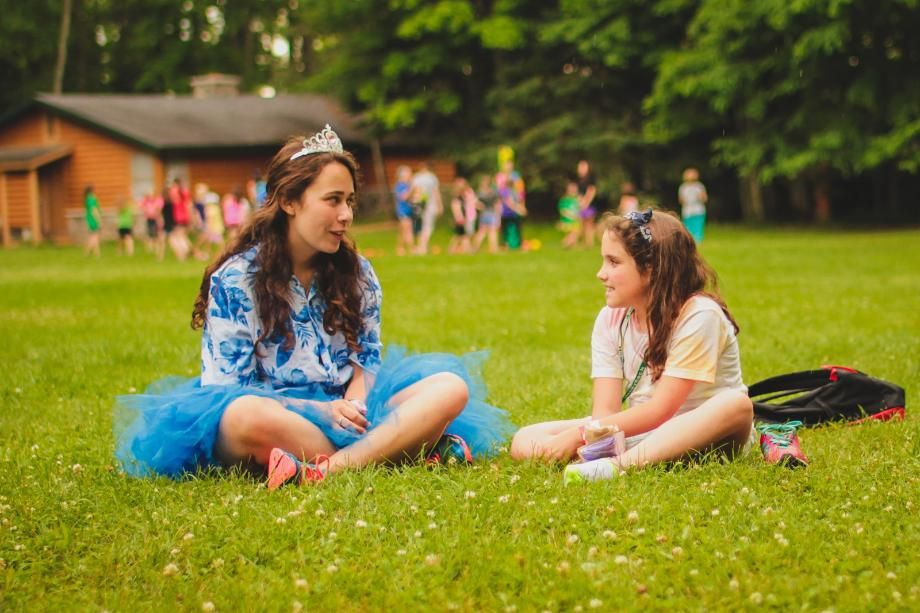 camper and counselor talking on the lawn
