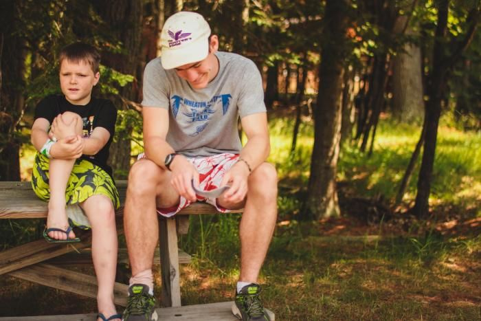 counselor and camper talk on wooden bench at HoneyRock in Three Lakes, WI