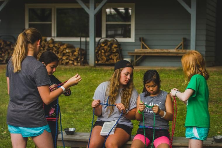 """Evenings are a mix of structured activities and free time. Cabins play group games with """"bro"""" or """"sis"""" cabins, spend time around a campfire, participate in a creative activity, or hang out by the lake and talk. It's simply time to be with others in the great outdoors. In this photo, a cabin of girls is learning how to tie knots."""