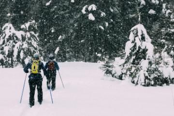 two students cross country skiing at honeyrock in three lakes, wi