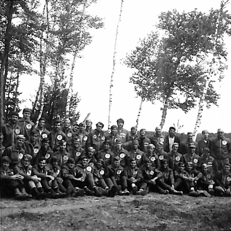 an early group of Vanguards sit by the lake