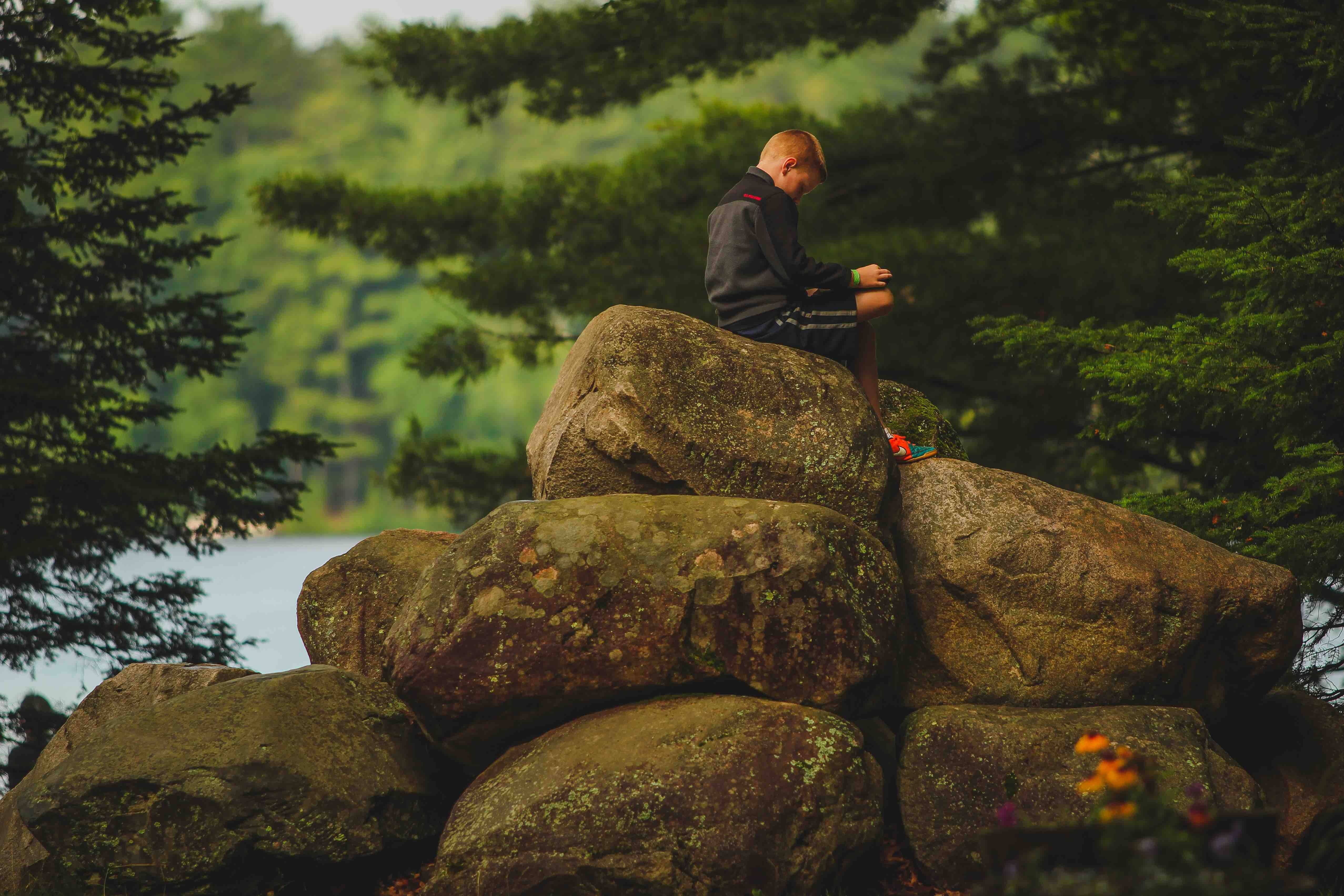 """Campers often find """"their spot"""" for this special time at HoneyRock. If you were here during Morning Watch, you'd see them spread out over Chrouser lawn, sitting next to a tree, or like this camper, ontop of one of the rock stacks!"""