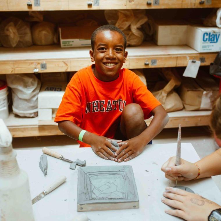 camper boy crafting in the ceramics studio