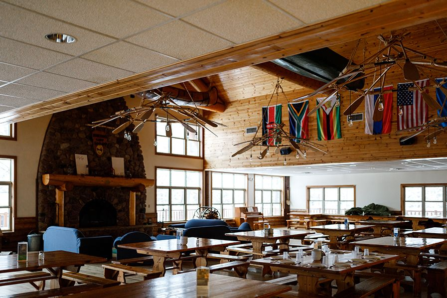 With a big stone fireplace, canoes hanging from the ceiling, and flags representing the home countries of our summer staff, the dining hall is a warm and homey place to gather and share a meal.