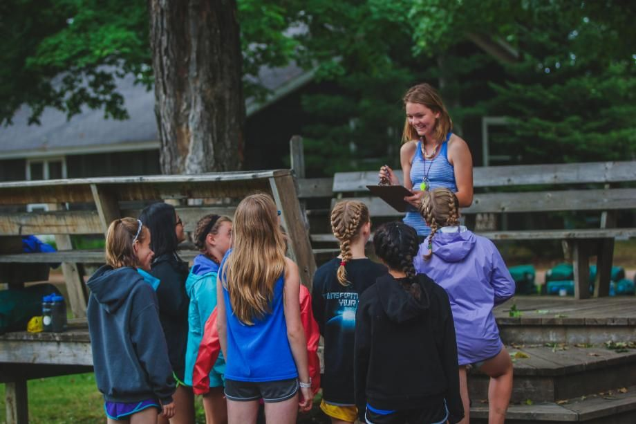 assistant counselor talks with campers