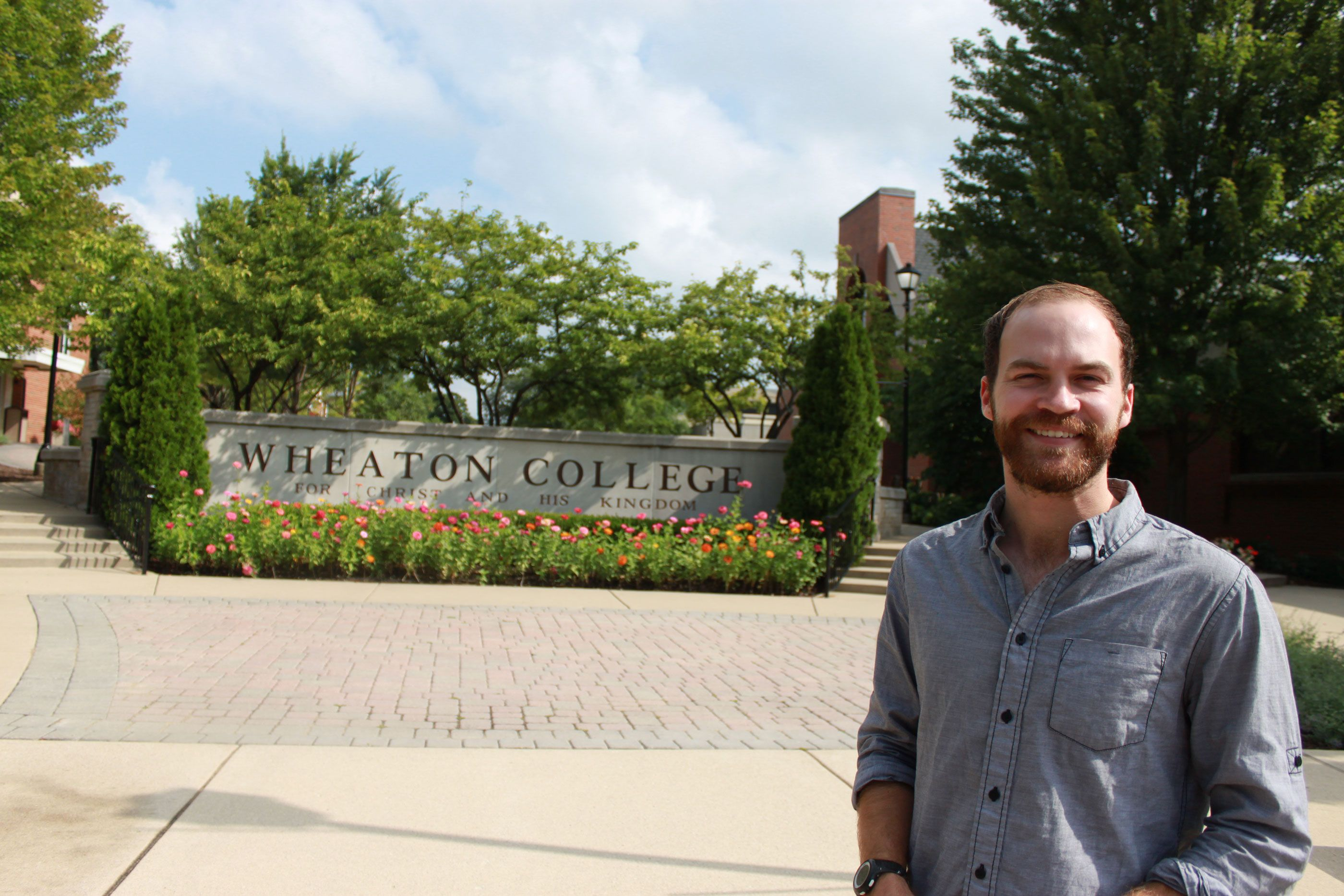 Michael Sawyer standing at Wheaton College sign