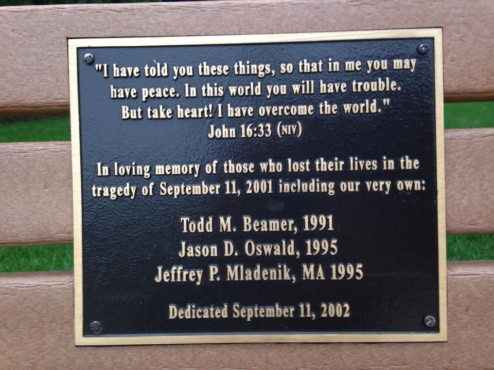 """On September 11, 2002, Wheaton College dedicated a commemorative plaque on a bench on campus in honor of the lives of the alumni lost on 9/11. The plaque reads: """"I have told you these things, so that in me you may have peace. In this world you will have trouble. But take heart! I have overcome the world."""" John 16: 33 (NIV). In loving memory of those who lost their lives in the tragedy of September 11, 2001 including our very own: Tood M. Beamer, 1991; Jason D. Oswald, 1995; Jeffrey P. Mladenik, MA 1995. Dedicated September 11, 2002."""