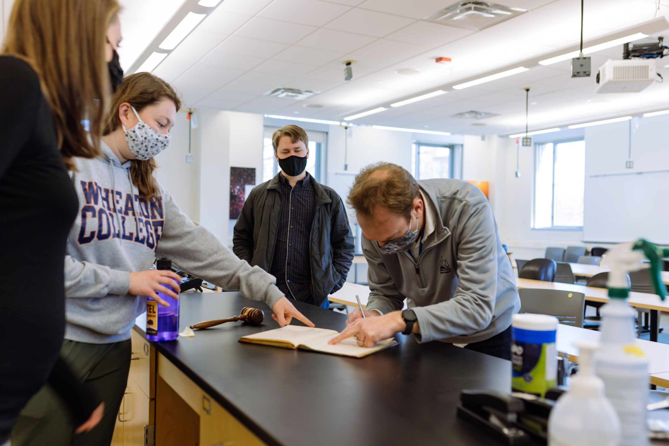 After the induction ceremony, students and faculty members look at the signatures from former and current members of the Sigma Pi Sigma honor society.