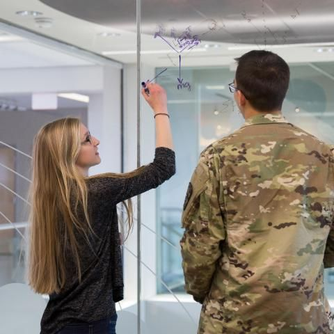Wheaton College Physics Students Writing on Glass Board in Meyer Science Center