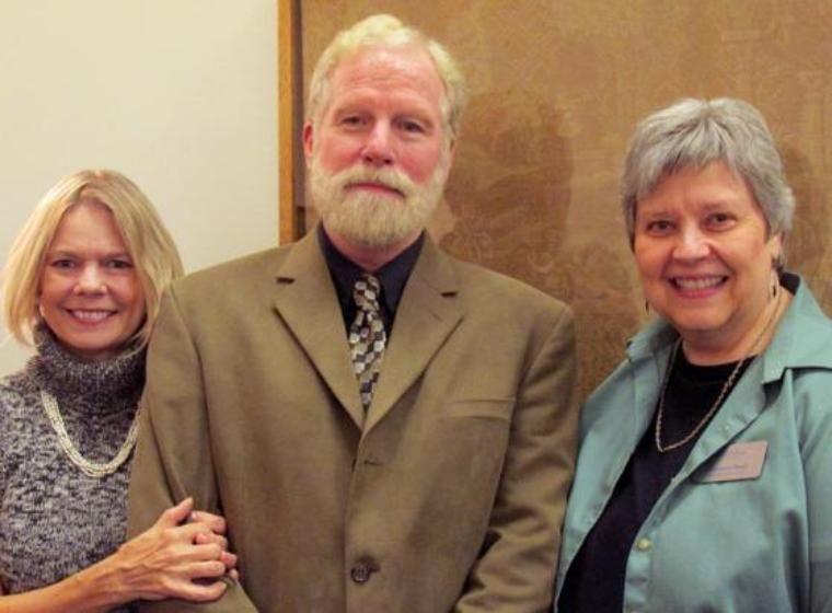 Man and 2 women surrounding him
