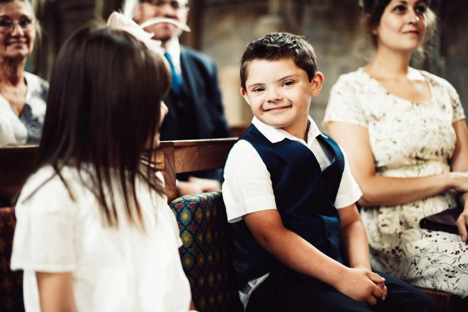 Boy with Down's syndrome sitting on pew in church