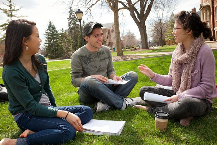 Photo of students sitting on lawn talking for left align content
